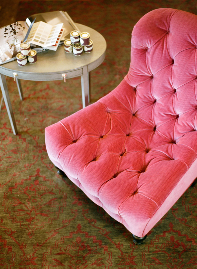 "Raspberry velvet tufted chair by Lee Industries - Farrow & Ball sample paint pots - Hand-knotted wool ""Tikapur"" rug"